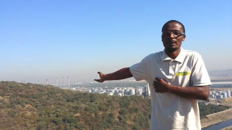 SDCEA staff Bongani Mthembu shows the Durban port landscape, filled with refineries, dumping sites, and other industrial plants.